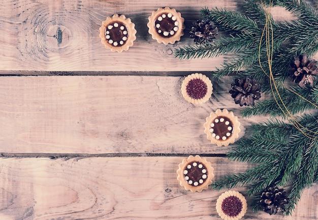 Kerstmisachtergrond met nette takken en kegels met koekjes Premium Foto