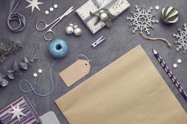 Kerstmisachtergrond met rode steenharten, verpakte giften, markeringen, koorden en snuisterijen op donker, exemplaar-ruimte Premium Foto
