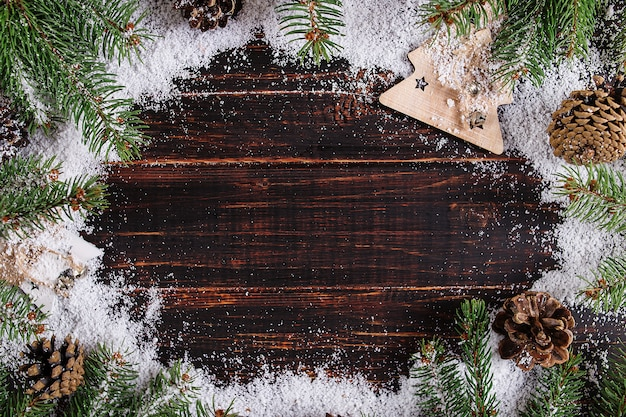 Kerstmisachtergrond, sparren en kegels op een houten lijst, verpletterd door witte sneeuw, exemplaarruimte, hoogste mening. Premium Foto