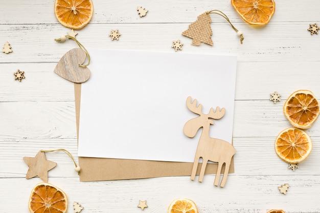 Kerstmisachtergrond van droge sinaasappelen, kerstmisdecoratie en lege witte kaart voor groeten op een houten lijst. sterren, harten en elanden. bovenaanzicht copyspace. Premium Foto