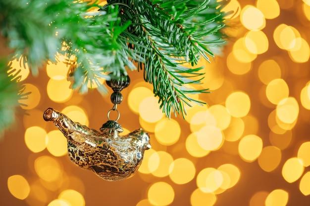 Kerstmisdecoratie het hangen op een sparrentak tegen kerstmislichten Premium Foto