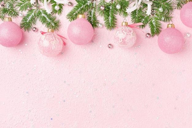 Kerstmisgrens van nieuwjaarornamenten, spar op roze achtergrond. Premium Foto