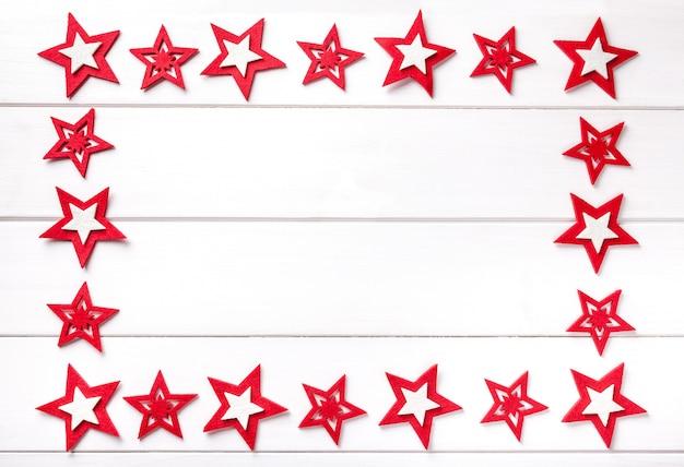 Kerstmiskader met rode sterren op whte houten achtergrond. Premium Foto