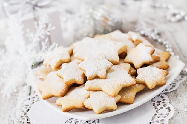 Kerstmiskoekjes en klatergoud op een houten lijst Premium Foto