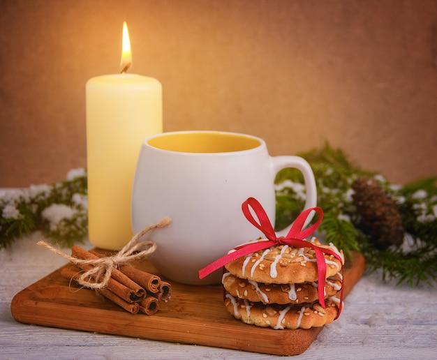 Kerstmiskoekjes met kop thee op houten lijst. kerst decoratie. Premium Foto
