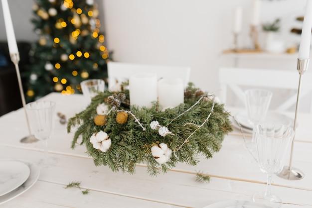 Kerstmiskroon met witte kaarsen op de feestelijke lijst Premium Foto