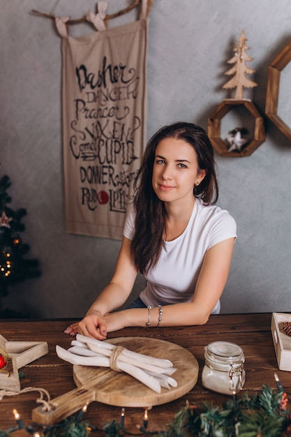 Kerstmisportret van jonge vrij donkerbruine vrouw bij gezellig huis Premium Foto