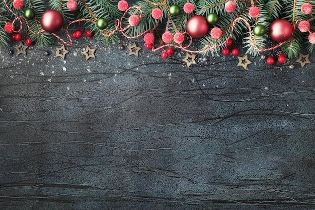 Kerstmisregeling met spartakjes, rode en groene snuisterijen en lichten op donkere, tekstruimte Premium Foto