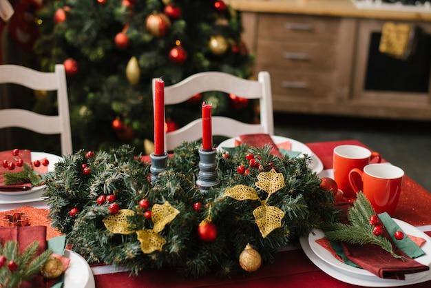 Kerstmissamenstelling met rode kaarsen op een feestelijke lijst met een rood tafelkleed Premium Foto