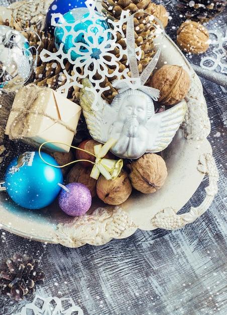 Kerstmissamenstelling van ballen, kegels en sneeuwvlokken in een metaalkom. vintage-stijl. toning Premium Foto