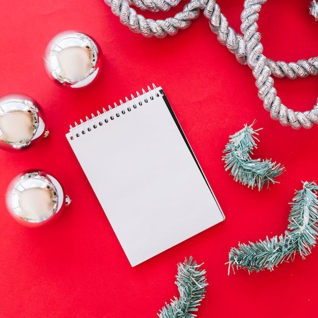 Kerstmissamenstelling van blocnote met glanzende snuisterijen Gratis Foto
