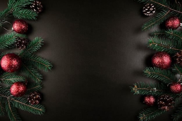 Kerstmissamenstelling van groene sparrentakken met rode snuisterijen Gratis Foto