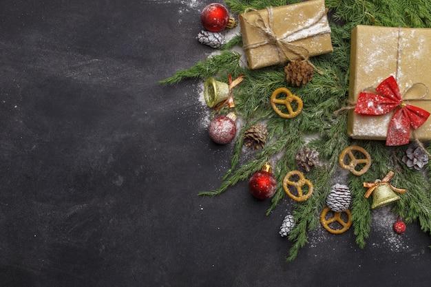 Kerstmissamenstelling van naaldtakken, decoratie en snoepjes op donkere achtergrond. plat leggen. bovenaanzicht natuur nieuwjaar concept. kopieer ruimte. Premium Foto