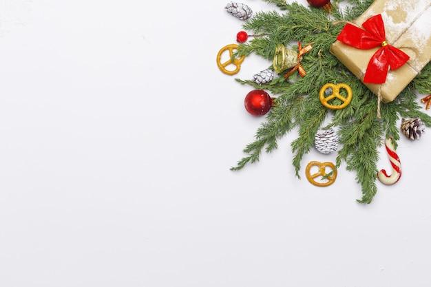 Kerstmissamenstelling van naaldtakken, decoratie en snoepjes op lichte achtergrond. plat leggen. bovenaanzicht natuur nieuwjaar concept. kopieer ruimte. Premium Foto