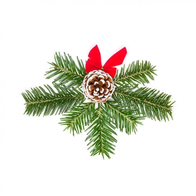 Kerstmissamenstelling van spartakken van rode die boog en denneappel op een witte achtergrond wordt geïsoleerd Premium Foto