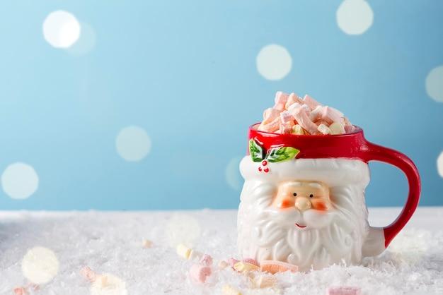 Kerstmissanta kopje warme chocolademelk met marshmallow op blauw. kerst eten en drinken concept Premium Foto