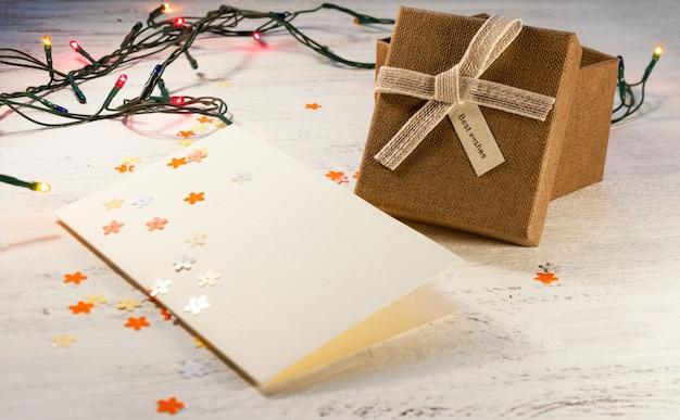 Kerstmisslinger met verlichting en een geschenkdoos met een lege ansichtkaart op een lichte achtergrond. kerstcadeau. Premium Foto