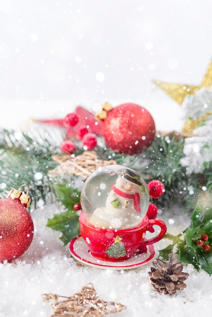 Kerstmissneeuwbol met pijnboomtakken en feestelijke decoraties op sneeuwtafel. kerstmis of nieuwjaar concept Premium Foto