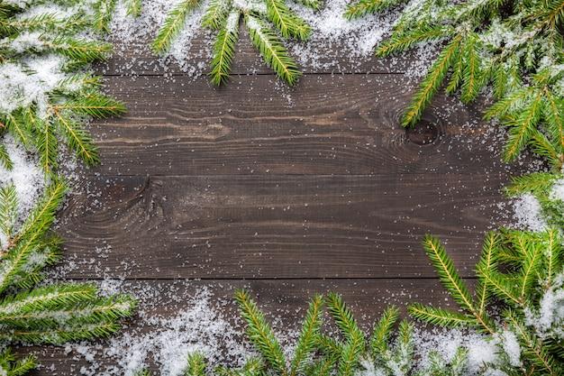 Kerstmisspar op een donkere houten raad met sneeuw. Premium Foto