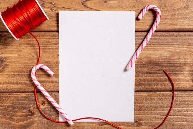 Kerstmisstokken en leeg blad op houten vloer Gratis Foto