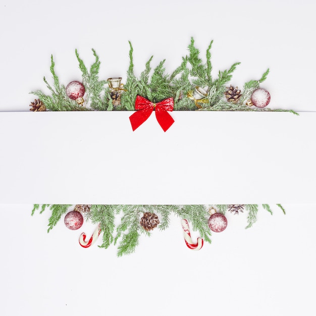 Kerstsamenstelling van naaldtakken, decoraties en snoepjes. plat leggen. bovenaanzicht natuur nieuwjaar concept. kopieer ruimte. Premium Foto