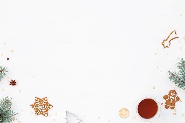 Kerstsfeer achtergrond met peperkoek, kopje thee en groene boom Premium Foto