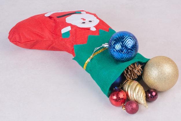 Kerstsok vol feestelijke ballen op witte ondergrond Gratis Foto