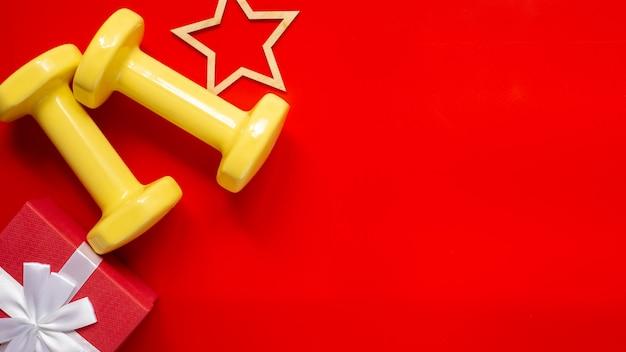 Kerstsport samenstelling met halters, houten ster beeldje, rode geschenkdoos met witte strik op rode achtergrond. Premium Foto