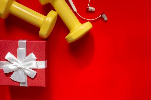 Kerstsporten samenstelling met halters, kleine oortelefoons, rode geschenkdoos Premium Foto
