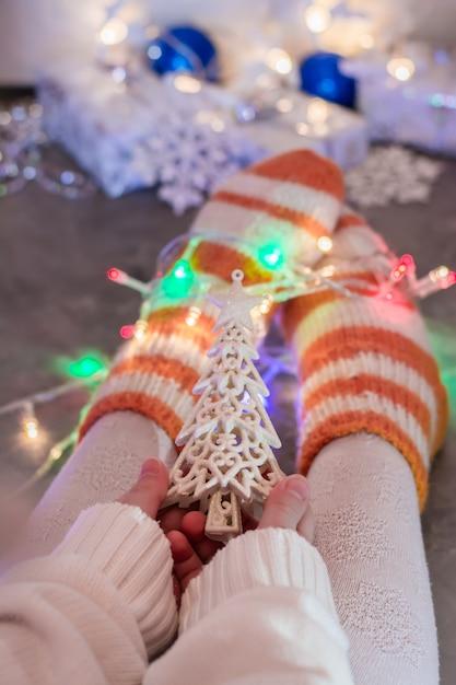 Kerststemming. een warm gekleed kind houdt een dennenornament in zijn handen Premium Foto