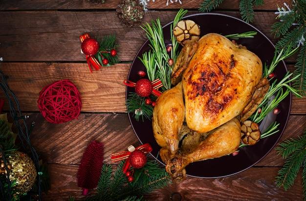 Kersttafel geserveerd met een kalkoen, versierd met helder klatergoud en kaarsen Gratis Foto