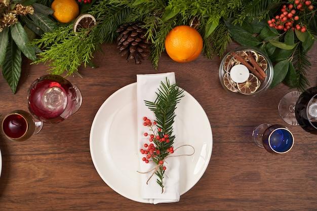 Kersttafel instelling met witte platen en kerstboom op houten tafel, bovenaanzicht. Premium Foto