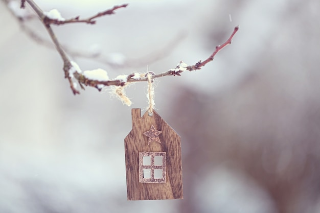 Kersttijd. een klein houten huis zwaait aan een tak en grote vlokken sneeuw vallen langzaam. Premium Foto