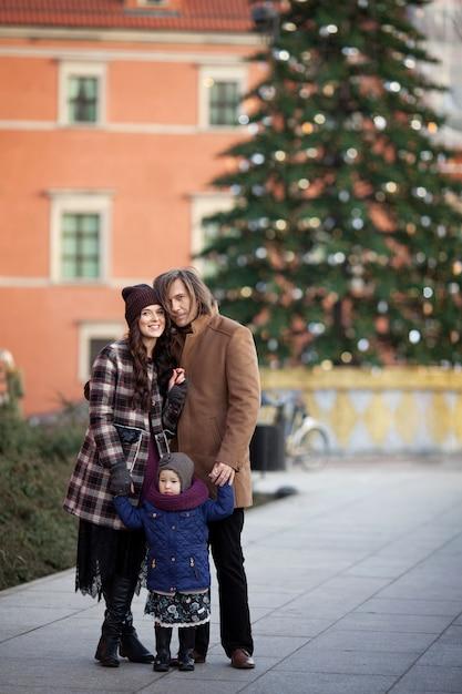 Kersttijd. gelukkige familie - moeder, vader en meisje lopen in de stad en plezier maken Premium Foto