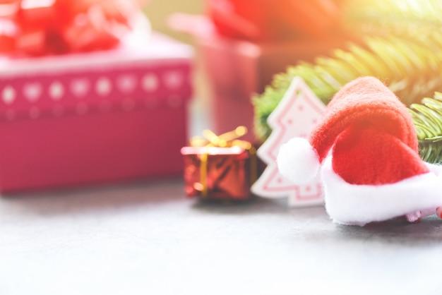 Kerstvakantie met kerstmuts en spar takken decoratie geschenkdoos en Premium Foto