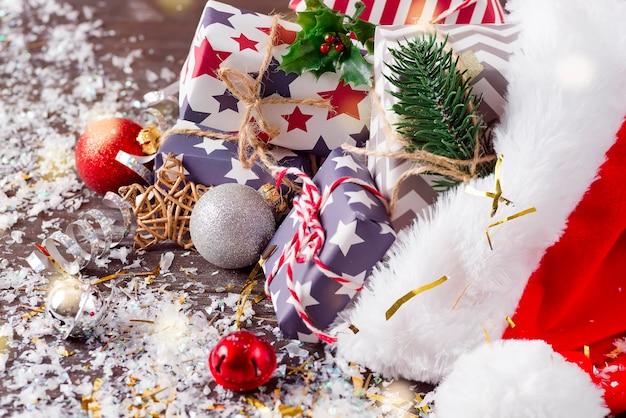 Kerstvakantie samenstelling met rode kerstmuts en geschenkdozen op houten achtergrond Premium Foto
