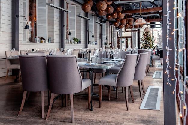 Kerstverlichting, decor, interieur modern restaurant, panoramische ramen, instelling, serveren banket, grijze textiel stoelen, serveertafels, wijnglas, borden, bestek. feestelijk nieuwjaar, winter Premium Foto
