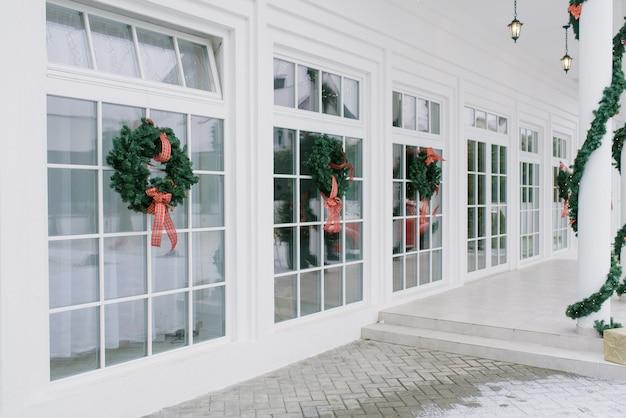 Kerstversiering: kransen met strikken op de witte franse ramen van een privéwoning Premium Foto