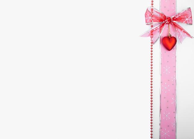 Kerstversiering verticaal geplaatst aan de zijkant van de afbeelding met copyspace op witte achtergrond, boog, hart, lint, Premium Foto