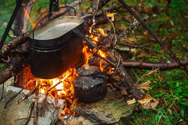 Ketel op statief boven vreugdevuur. koken van voedsel op de natuur. diner buitenshuis. brandhout, takken en kreupelhout in brand. actieve rust. camping. atmosferisch vuur. Premium Foto