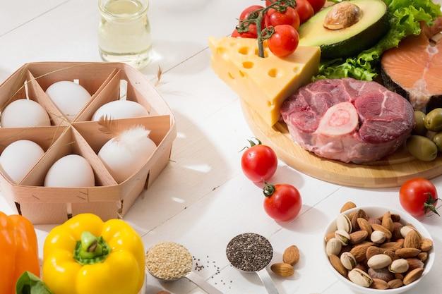 Ketogeen koolhydraatarm dieet - voedselselectie op witte muur Gratis Foto