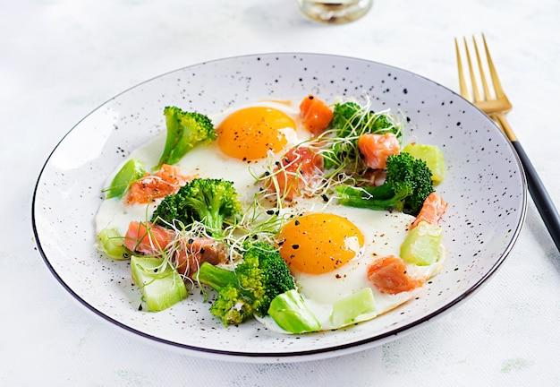 Ketogeen / paleodieet. gebakken eieren, zalm, broccoli en microgreen. keto-ontbijt. brunch. Gratis Foto
