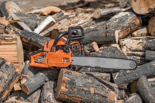 Kettingzaag die op een hoop brandhout in de tuin staat Premium Foto