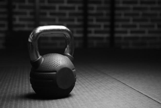 Kettlebell gewichten in een sportschool in zwart en wit Premium Foto