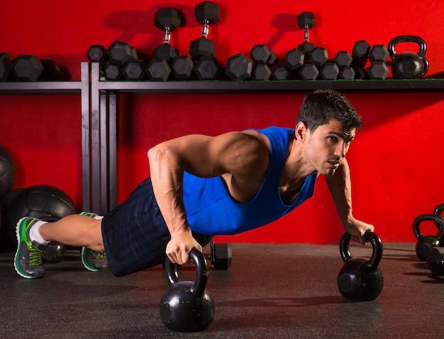 Kettlebells push-up man krachttraining gymnastiek Premium Foto