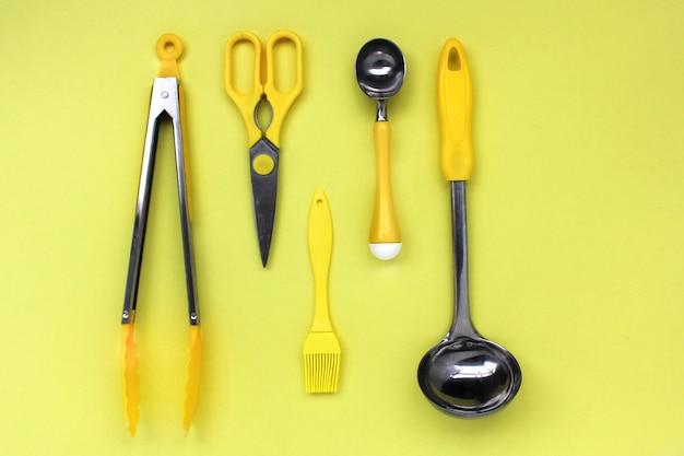Keuken pollepel accessoires, schaar, tang, borstel, gele ijs lepel op een gele achtergrond Premium Foto
