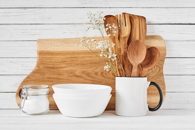 Keukengereedschap en snijplank op witte tafel Premium Foto