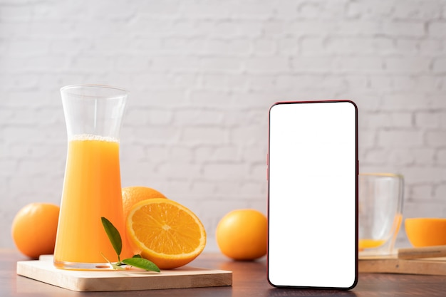 Keukentafel met leeg scherm slimme telefoon, mobiele telefoon, tablet en kruik sinaasappelsap. Premium Foto