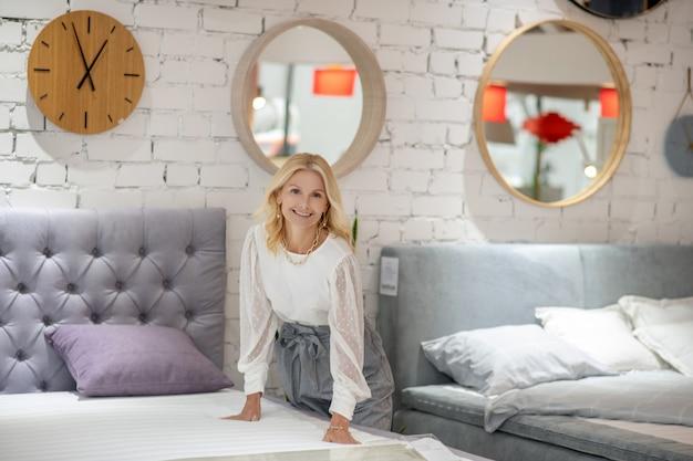 Keuze, beslissing. vrouw in een witte blouse staande buigen naar het bed, het aanraken van de matras, op zoek blij. Premium Foto