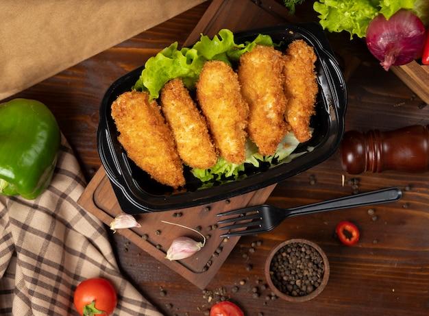 Kfc-stijl gebakken kipnuggets-afhaalmaaltijd in zwarte container Gratis Foto